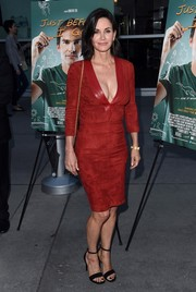 Courteney Cox flaunted her ageless figure in a tight red Jitrois suede dress with a plunging neckline at the LA screening of 'Just Before I Go.'