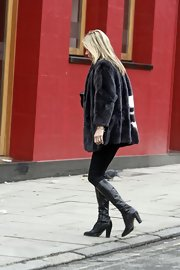 Kate Moss accessorized her all-black look with a pair of leather knee-high boots.