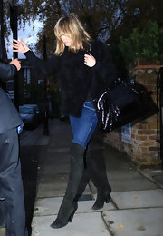 Supermodel Kate moss made her way through London, looking surprisingly chic in her over-the-knee boots and patent leather clutch.