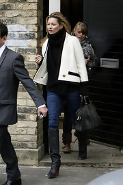 Kate Moss looked effortlessly chic in a white swing coat with black and red piping.