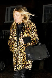 Kate Moss accessorized her bold leopard print coat with a chic black suede bag.