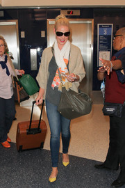Katherine Heigl layered a loose beige cardigan over a gray tee for a her airport look.
