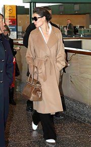 Katie donned a classic camel wrap coat while on her way to the airport.