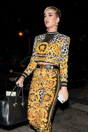 Katy Perry teamed a black leather belt with print pants and a crop-top, all by Versace, for a night out.