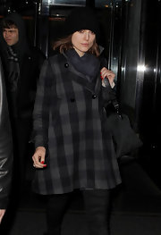 Keira Knightley beat the winter chill with a charcoal scarf and plaid swing coat while hitting up the airport.