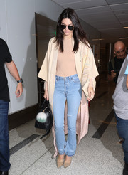 Kendall Jenner completed her airport look with a pair of high-waisted jeans.