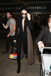 Kendall Jenner must have turned plenty of heads at LAX when she wore this plunging black T by Alexander Wang lace-up bodysuit with a pair of skinny jeans.