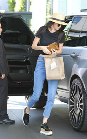 For her bag, Kendall Jenner chose a small tan suede clutch by Saint Laurent.