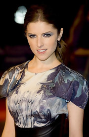 To recreate Anna Kendrick's bright-eyed look, use a medium to dark blue shadow or eye pencil to line upper and lower lash lines, then smudge slightly with fingertips. Next, sweep a light blue shade over lids and blend up into creases. To highlight, add a touch of icy blue shadow along the brow bone and into the inner corners of the eyes. To finish the look, apply some volumizing mascara.