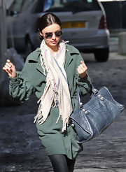 While attending the weeks fashion shows in Paris Miranda made a stylish appearance in a green jacket and blue crocodile tote bag. Her scarf added a nice additional color, which gave her a layered look.