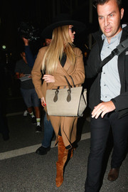 Khloe Kardashian bundled up in a classic tan wool coat for a flight.