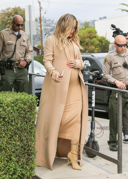 Khloe Kardashian layered a beige duster over a matching maternity dress for a day of shopping.