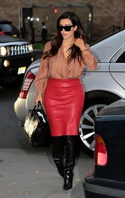 Thigh-high leather boots toughened up Kim's ladylike look.