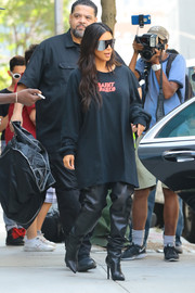 Kim Kardashian completed her outfit with slouchy black thigh-high boots by Balenciaga.