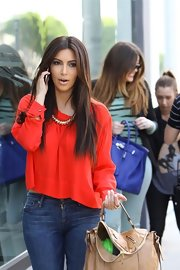 Kim Kardashian's Belle Noel gold collar necklace went beautifully with her red blouse.