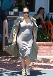 Kim Kardashian styled her simple dress with a beige trenchcoat by Isabel Marant.
