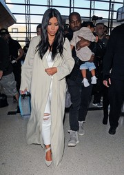 Kim Kardashian donned a pale-gray duster and ripped jeans for a flight out of LAX.
