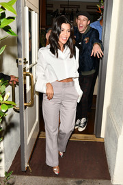 Kourtney Kardashian teamed her top with gray slacks.