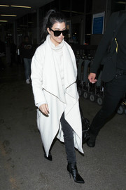 Kourtney Kardashian bundled up in a stylish white shawl-collar coat for a flight.