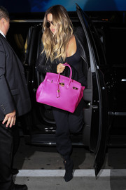 Khloe Kardashian accessorized with a hot-pink Hermes Birkin for a pop of color to her all-black airport look.