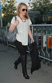 Kylie Minogue paired her over the knee boots with a grey patent leather bag.