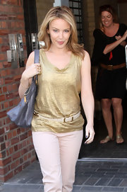 The Aussie popstar accessorized her metallic top with a thin leather belt featuring gold hardware.