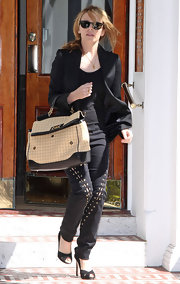 Kylie Minogue always keeps her style game on point. She was seen leaving her London home in a stylish pair of lace up pants and a leather tote bag.