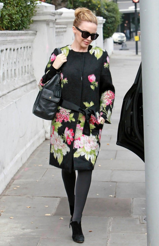 Kylie Minogue steps out in a flowery robe but is still all smiles.