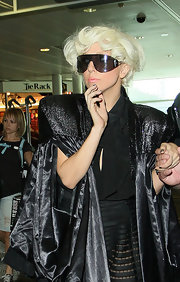 Lady Gaga paired her all-black ensemble with shield sunglasses while making her way through Heathrow airport.