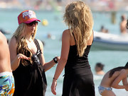 Avril tops off her look with an orange and pink trucker hat while out with family at the beach.