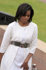looking stunning in white, Mrs. Obama is going for a fitted look and wears a metalic belt.