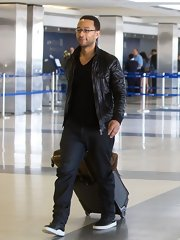 John Legend traveled in style with a simple black bomber jacket paired with dark jeans.
