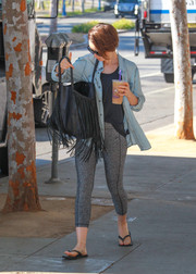 Lily Collins styled her sporty outfit with a mega-fringed shopper bag.