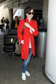 Lily Collins sealed off her travel attire with a pair of white Superga canvas sneakers.