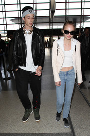 Lily-Rose Depp layered a cream-colored moto jacket over a white crop-top for a flight out of LAX.