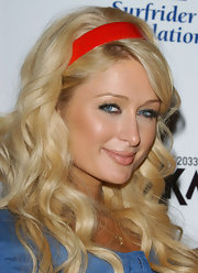 Paris Hilton wore her long curled locks pulled back with a red headband.