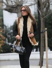 Elizabeth Hurley carried a petite black leather tote with gold hardware.