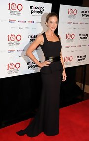 Emily Blunt stunned in a black floor-length gown that featured a belted waist and peplum detail.