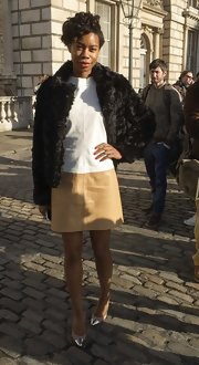 Tolula Adeyemi dressed up her white and tan sheath dress with a glamorous black fur coat.