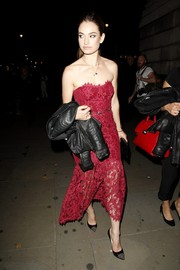Lily James was spotted out and about during London Fashion Week wearing a red lace strapless dress by Marchesa Notte.