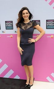 Kelly Brook's dark purple fitted dress featured elegant black lace detailing on the neck and sleeves.