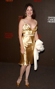 Madeleine paired her shining gold ensemble with a pair of marigold ankle-wrap kitten-heel pumps.