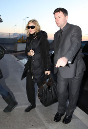 Madonna went for an all black look as she traveled through Heathrow airport. While her outfit might not have been a stand out, her large perforated leather tote bag was.