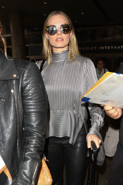 Margot Robbie shielded her eyes with a pair of oversized round shades while facing the LAX paparazzi.