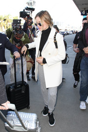 Margot Robbie caught a flight looking cozy in a white wool coat.