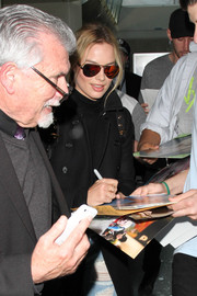 Margot Robbie looked fierce in mirrored red aviators by Westward Leaning as she arrived on a flight at LAX.
