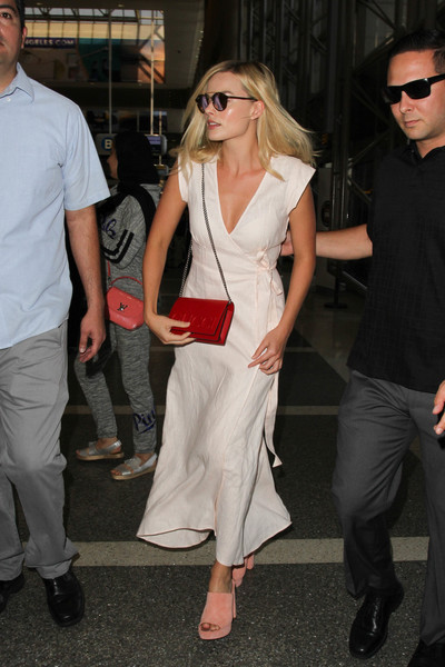 Margot Robbie pulled her airport look together with a chic red chain-strap bag by Gucci.