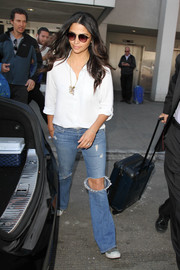 Camila Alves chose a pair of torn jeans to complete her airport look.