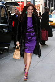 Debra opted for bright colors, wearing a purple dress and vibrant platform sandals.
