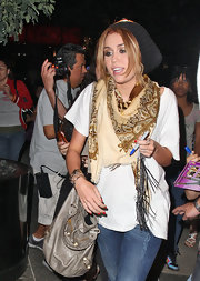Miley amped up her casual look with a patterned scarf that wrapped around her neck.